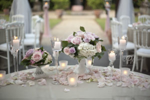 fiori con petali e candele su tavolo