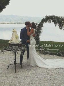 sposi davanti torta con lago sullo sfondo