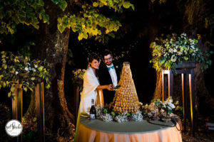 torta di bigne con sposi che la tagliano