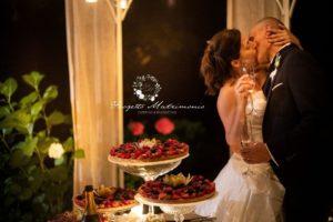 sposi si baciano davanti dolci
